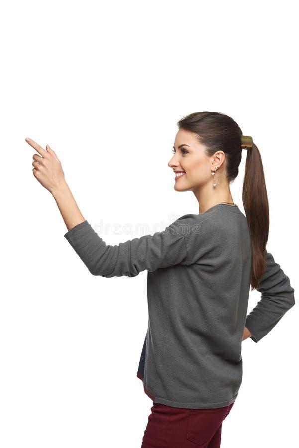 Sidosikt av kvinnan som pekar på kopieringsutrymme arkivfoton