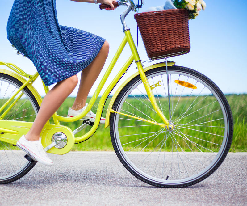 Sidosikt av kvinnan som rider den retro cykeln i bygd arkivbilder