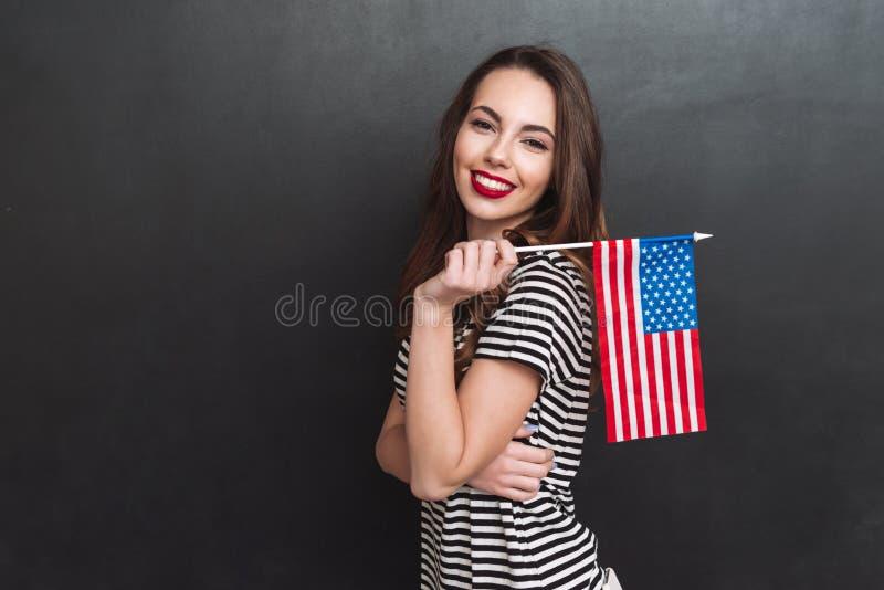 Sidosikt av kvinnan som rymmer USA flaggan arkivfoto