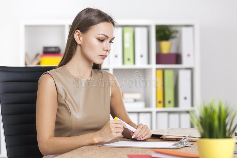 Sidosikt av kvinnan som ser skrivplattan royaltyfri foto
