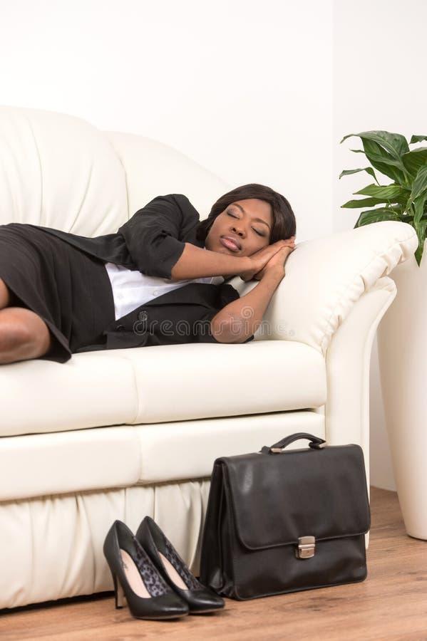 Sidosikt av kvinnan som sover på soffan royaltyfri foto