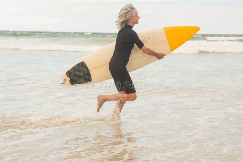 Sidosikt av kvinnaspring med surfingbrädan på kust arkivbild
