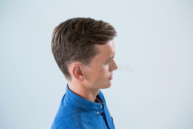 Sidosikt av mannen i blå skjorta royaltyfria foton