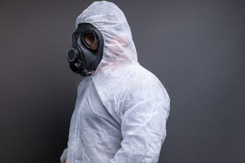 Sidosikt av mannen med gasmasken i skyddande total- dräkt mot grå bakgrund royaltyfria foton