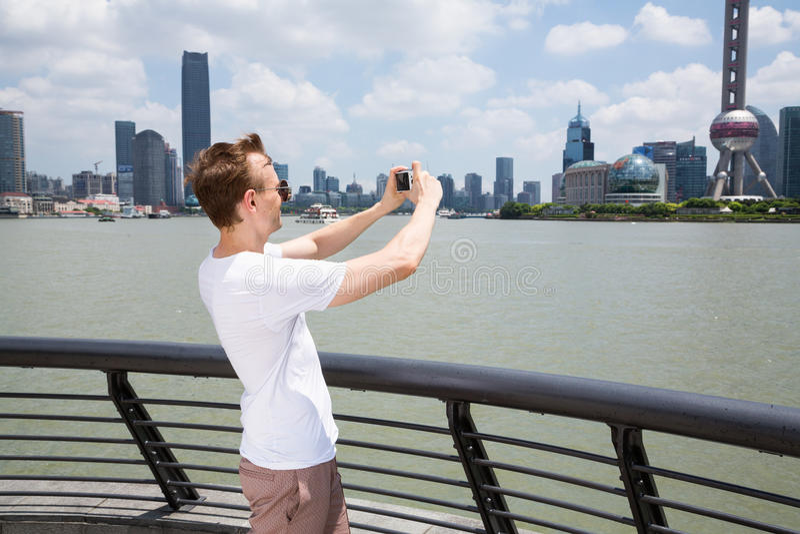 Download Sidosikt Av Mannen Som Fotograferar Byggnader, Medan Stå Vid Räcket I Shanghai Fotografering för Bildbyråer - Bild av oklarhet, ytter: 78731391