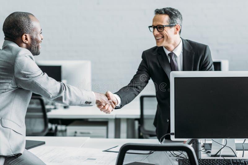 sidosikt av multiehtnic affärskollegor som skakar händer arkivbild
