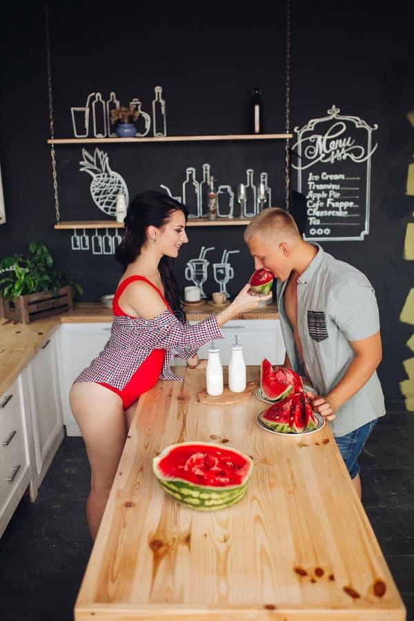 Sidosikt av par som står i kök och delar mål royaltyfria foton