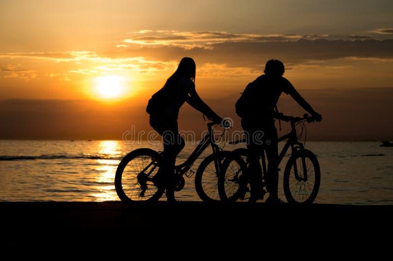 Sidosikt av par som står på kusten med deras cyklar och tycker om solnedgång royaltyfri fotografi
