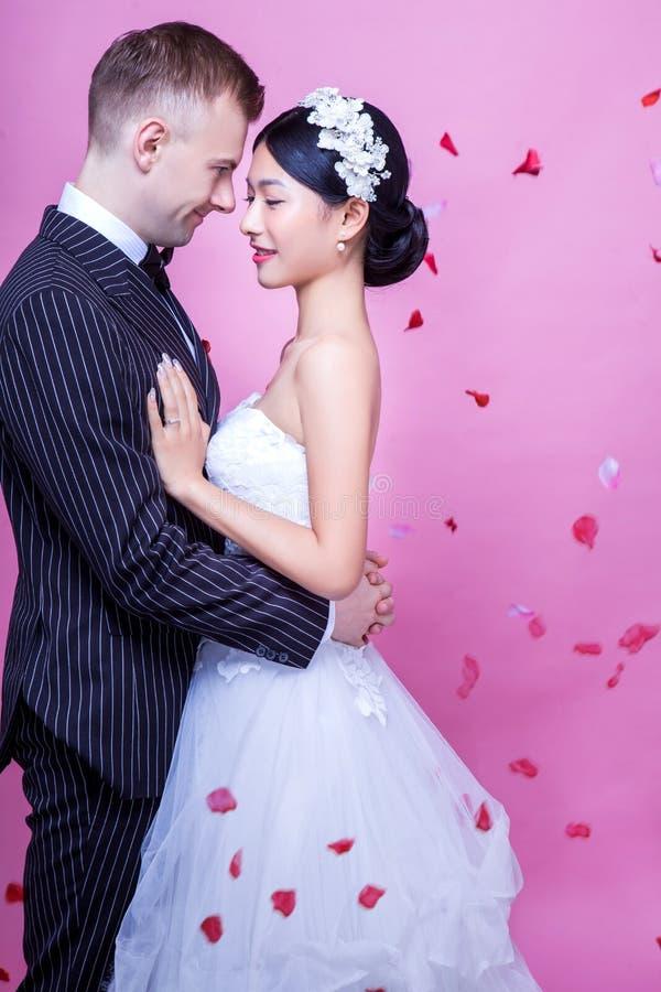 Download Sidosikt Av Romantiska Brölloppar Som Omfamnar Mot Rosa Bakgrund Arkivfoto - Bild av händelser, bild: 78732286