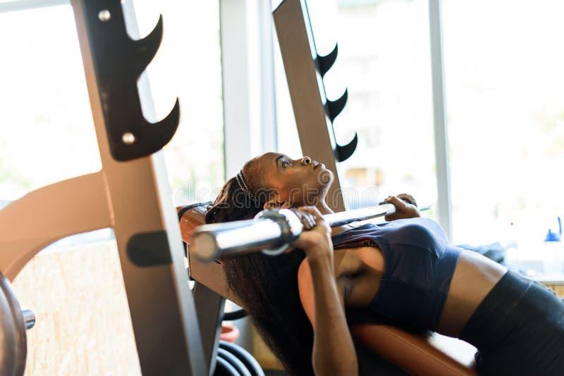 Sidosikt av sexig ursnygg afrikansk amerikankvinnautbildning med skivstången på idrottshallen royaltyfria foton