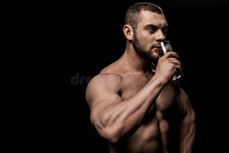 Sidosikt av shirtless dricksvatten och att se för man bort royaltyfri bild