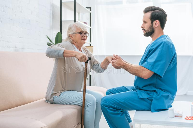 sidosikt av sjukskötaren som hjälper den höga kvinnan fotografering för bildbyråer