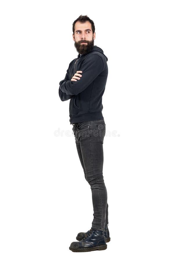 Sidosikt av skäggig punker som bär den med huva tröjan med korsade armar som bort ser royaltyfri fotografi