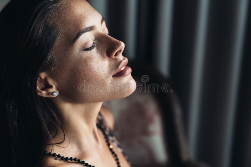 Sidosikt av ståenden av den sexiga sinnliga brunettflickan med stängda ögon och naturligt smink royaltyfria bilder