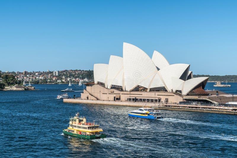Sidosikt av Sydney Opera House med färjor framme, Australien royaltyfri foto