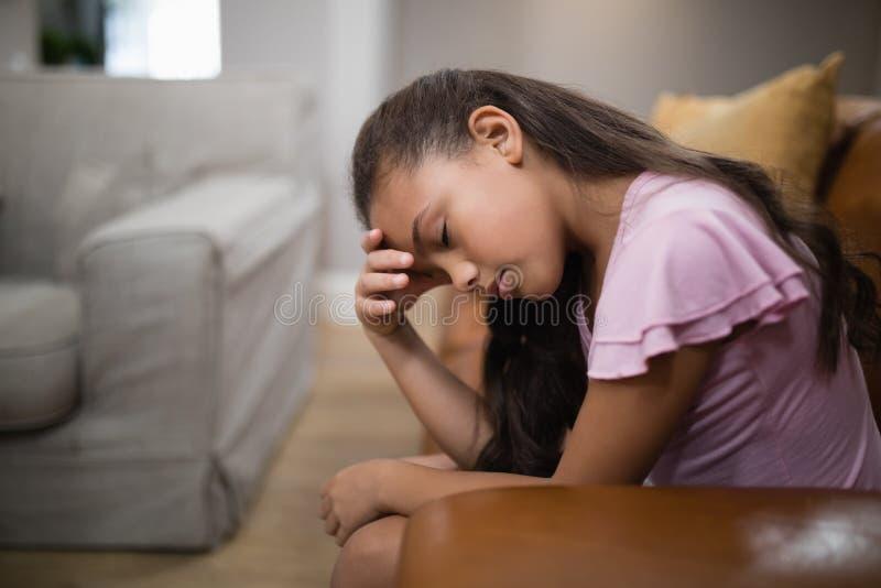 Sidosikt av trött flickasammanträde på soffan arkivbild