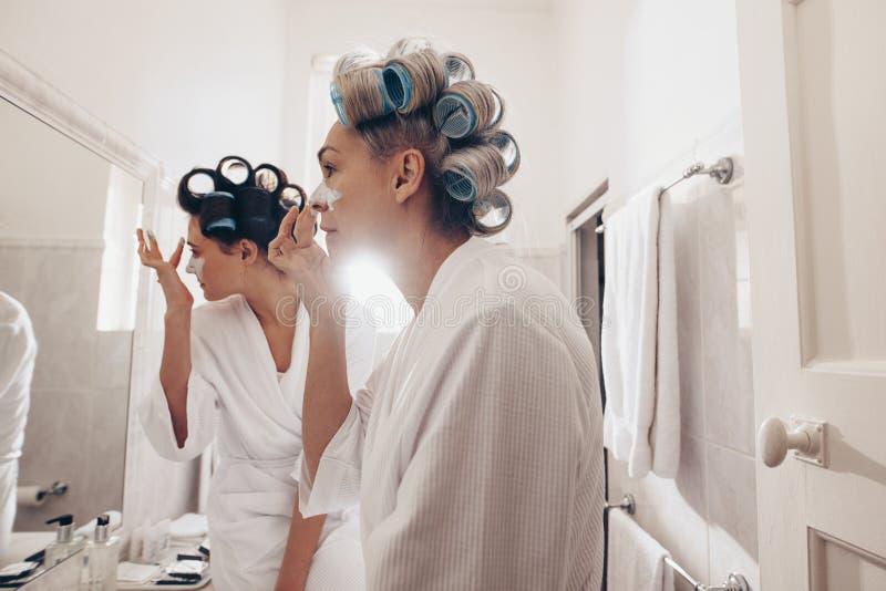 Sidosikt av två kvinnor i badrockar som applicerar kräm på framsidan som framme står av spegeln Kvinnor med lockiga rullar som kl fotografering för bildbyråer