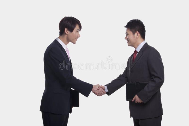 Sidosikt av två le affärsmän som skakar händer, studioskott royaltyfri bild