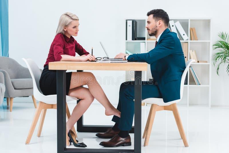 sidosikt av unga par av affärsfolk som ser de, medan arbeta tillsammans och flörta under tabellen arkivfoto