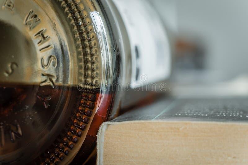 Sidosikt av whiskygravyr på en flaska, bredvid en häftad bokbok med rum för text arkivfoton