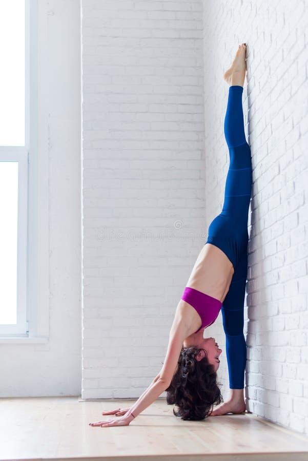 Sidosikt av yrkesmässig praktiserande yoga för kvinnlig idrottsman nen som sträcker henne kalvar, knäsena, lår som gör att stå de arkivbild