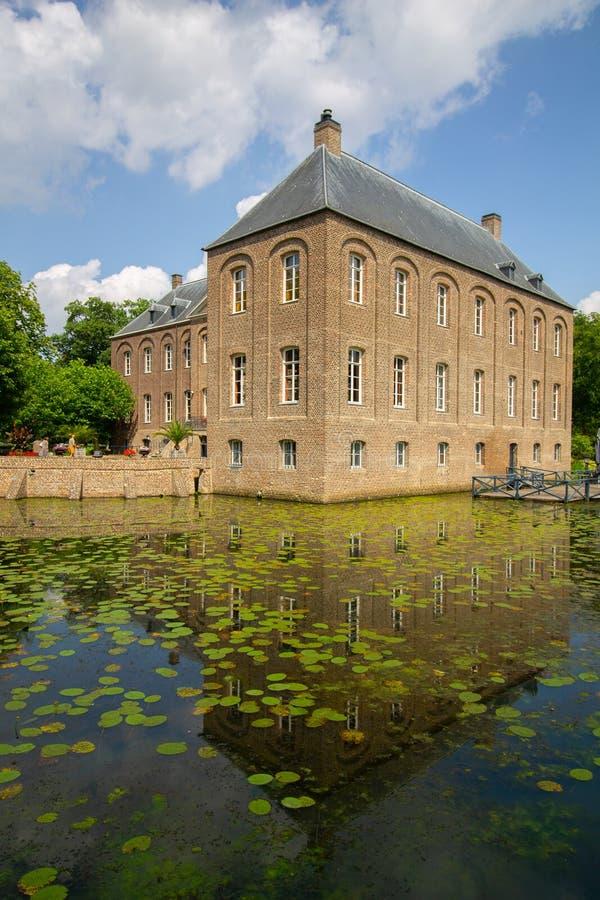 Sidosikt från slotten Arcen som är reflekterande i vatten med lelies royaltyfri foto