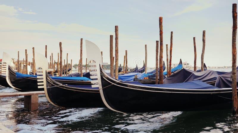 Sidosikt: Gondoler på pir Mot cityscapen av Venedig fotografering för bildbyråer