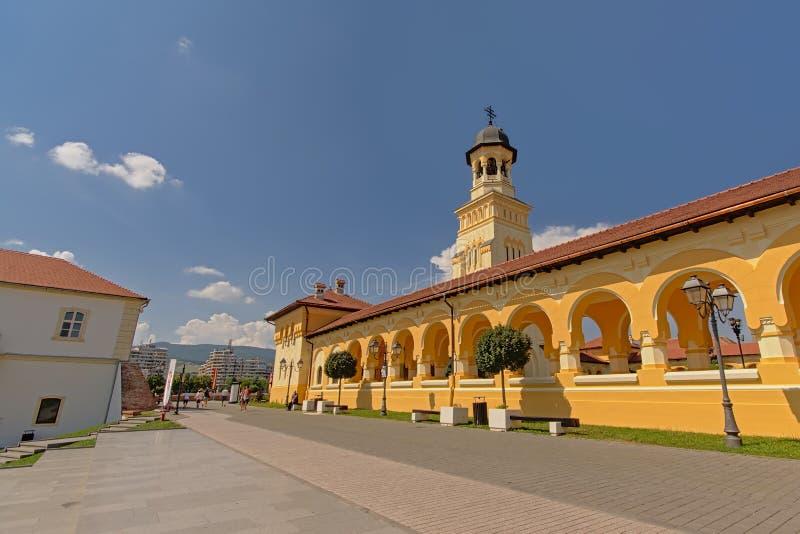 Sidosikt på den ortodoxa kröningdomkyrkan i rumänsk nationell stil Alba Iulia, med berg i bakgrunden royaltyfria bilder