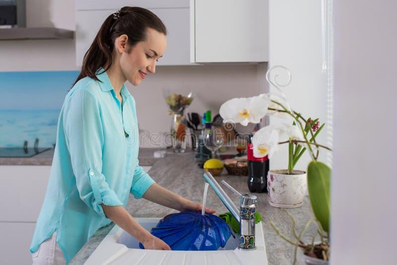 Sidosikt på kvinna i turkosskjortan i inre av köket på blåtten för vasktvagningmaträtt i det mjuka ljuset från royaltyfria foton