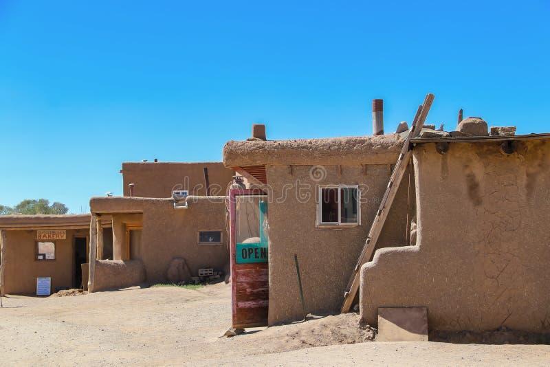 Sidosikten av Adobegyttjabyggnader i en pueblo i den sydvästliga USA, med shoppar med dörrar som är öppna för att sälja lokala ha arkivfoton