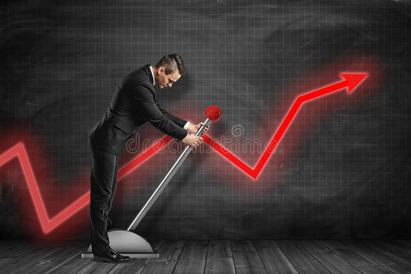 Sidosikten av affärsmannen som ner ser och drar den stora spaken nära svart graf, härskade väggen med den röda grafpilen på den royaltyfria foton