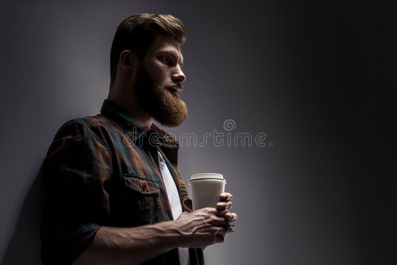 Sidosikten av barn uppsökte mannen som dricker morgonkaffe arkivfoto