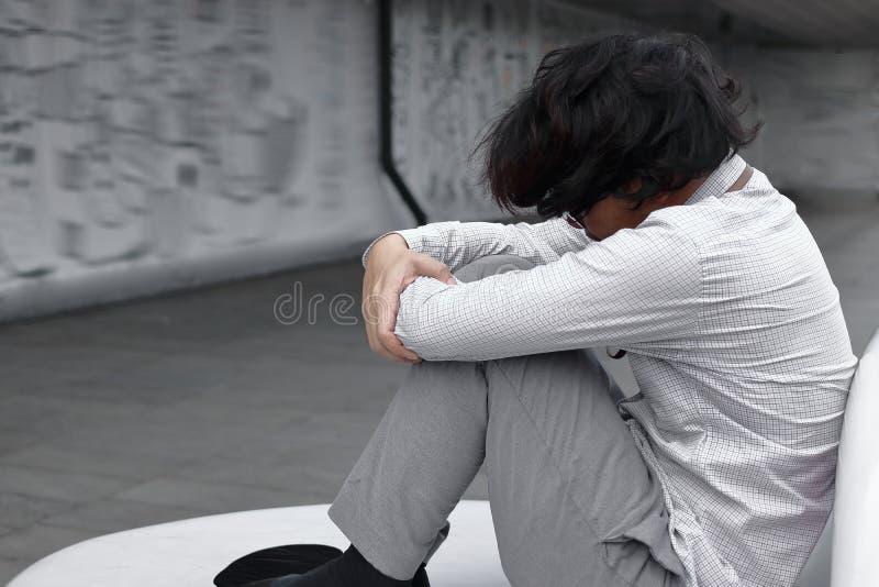 Sidosikten av den förvirrade utmattade unga asiatiska affärsmannen sitter och kramar hans knä upp till bröstkorgen royaltyfria bilder