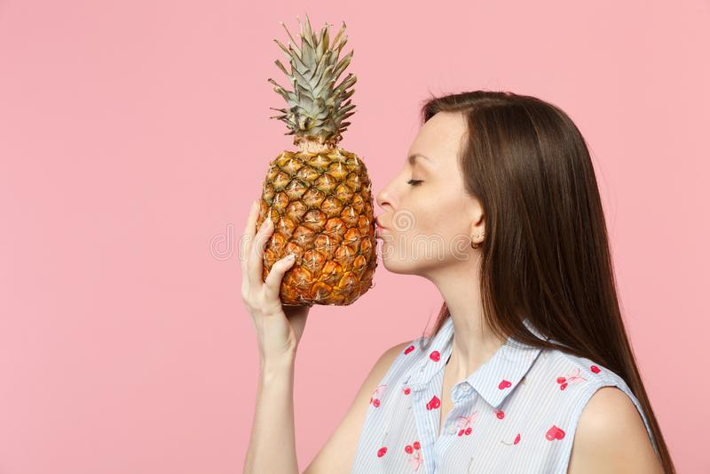 Sidosikten av den unga kvinnan i sommarkläder rymmer att kyssa ny mogen ananasfrukt som isoleras på den rosa pastellfärgade vägge royaltyfria bilder