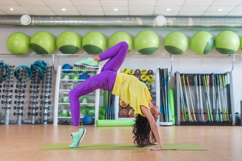 Sidosikten av den unga kvinnliga idrottskvinnan som gör yogaövningsanseende i hjul, poserar i idrottshall arkivfoton