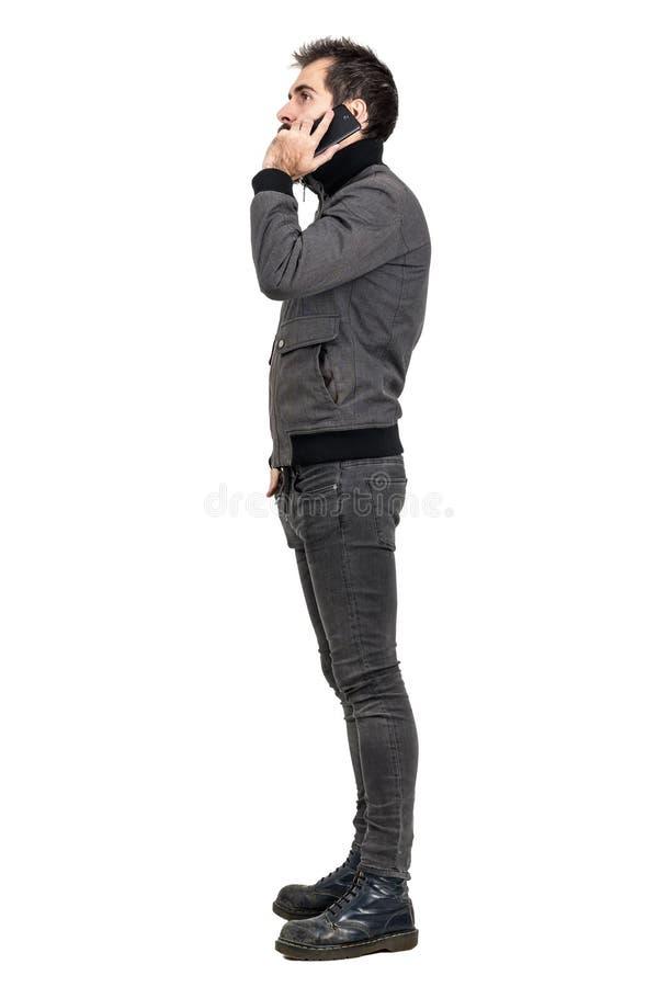 Sidosikten av den unga skäggiga mannen i grå färger klår upp samtal på mobiltelefonen arkivbilder