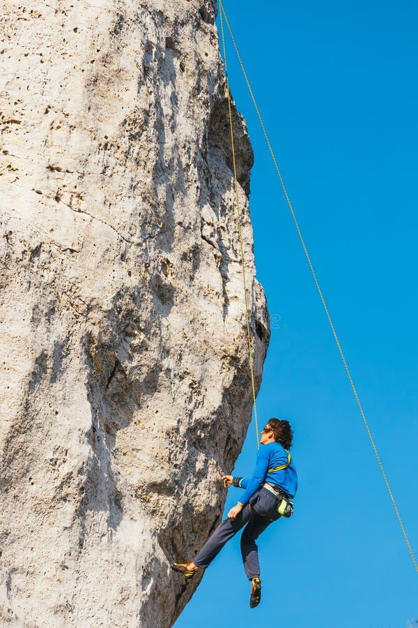 Sidosikten av den vuxna mannen vaggar klättraren på lodlinjelägenhetväggen med fattig lättnad arkivfoto