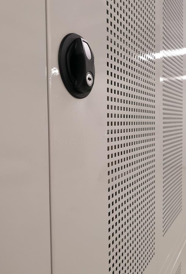 Sidosikten av ett skåp med ingreppsraster och en svart säkerhet pläterar hållaren för en tangent arkivbild