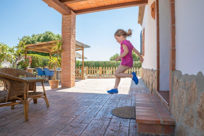 Sidosikten av fyra år gammal blond flicka med den rosa skjortan som hoppar eller tar ett stort, hoppar, från den yttre dörröppnin royaltyfria foton