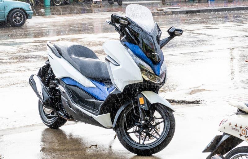Sidosikten av parkering 2018 för denblått Honda Forza 300 motorcykeln på sida går, i att regna dag arkivbild