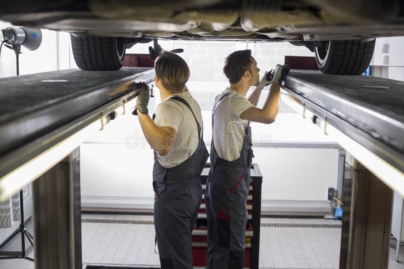 Sidosikten av underhållsteknikerer som undersöker bilen i reparation, shoppar royaltyfri bild