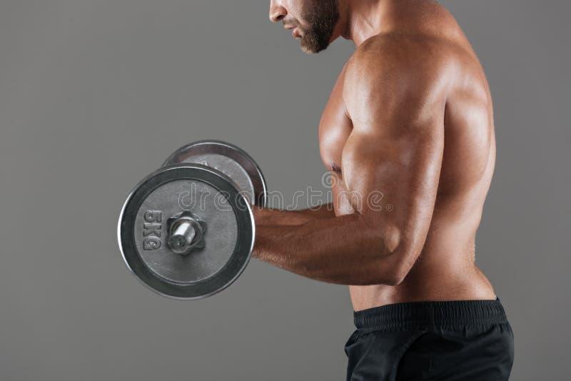 Sidosikten kantjusterade bild av en muskulös shirtless man arkivfoto