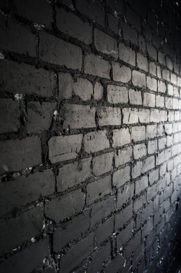 Sidosikten på den svarta tegelstenväggen tände vid ljus från fönstret arkivbilder
