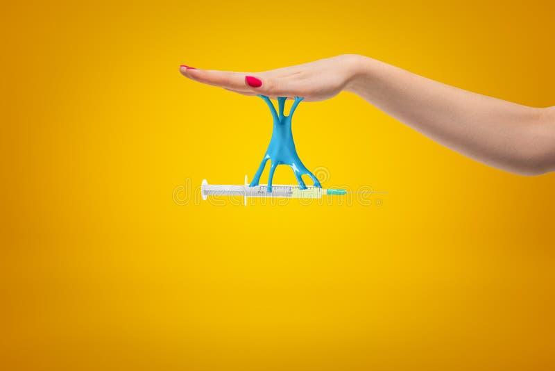 Sidoskördcloseupen av kvinnans injektionssprutan för handinnehavet, som klibbas till henne, gömma i handflatan med blå klibbig sl arkivfoton