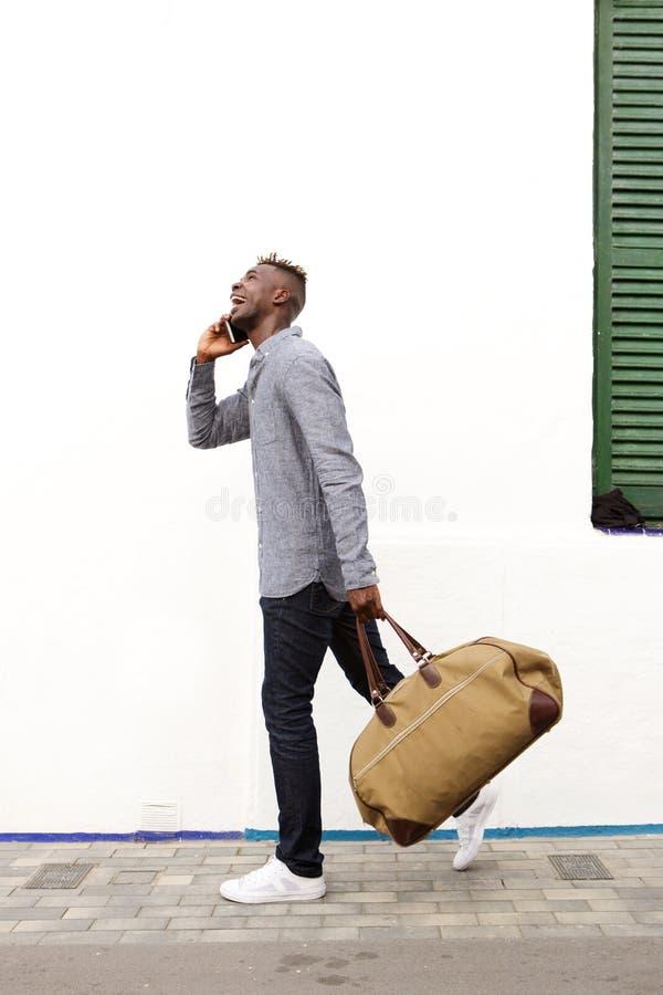 Sidostående av den resande unga afrikanska mannen som går och talar på mobiltelefonen arkivfoton