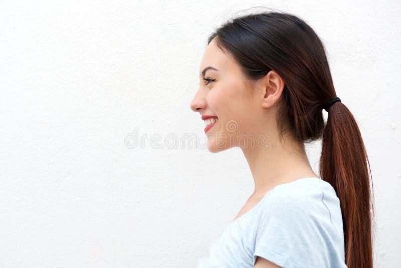 Sidostående av den sunda unga kvinnan med långt le för hår arkivfoto