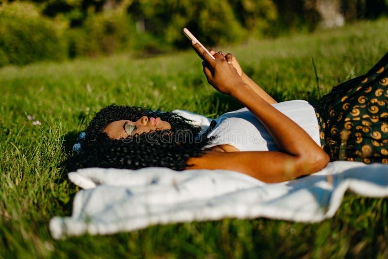 Sidostående av den unga attraktiva afrikanska flickan med skuggor för grönt öga som lägger på gräset och att bläddra och att prat arkivbild