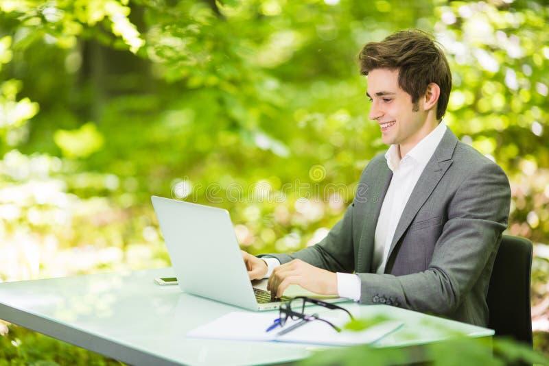 Sidostående av den unga stiliga affärsmannen i dräkten som arbetar på bärbara datorn på kontorstabellen i gröna Forest Park ägand arkivfoton