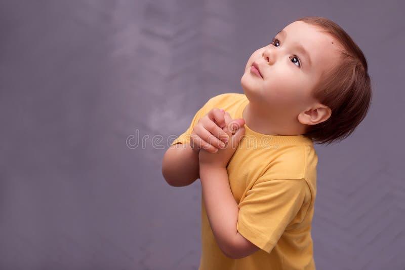 Sidostående av lite pojken som tigger eller frågar för något mot grått målat golv royaltyfri bild