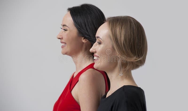 Sidostående - två säkra affärskvinnor arkivfoto